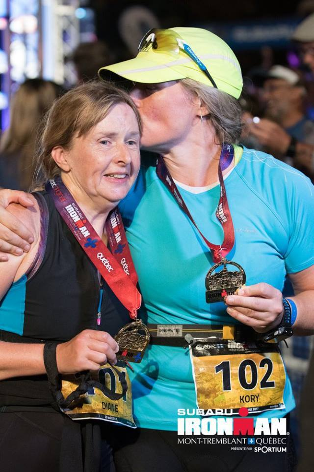 Diane and Kory hugging at finish wearing medals