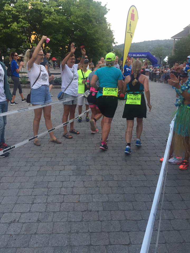 Diane and Kory running with people cheering, approaching arch to complete first loop